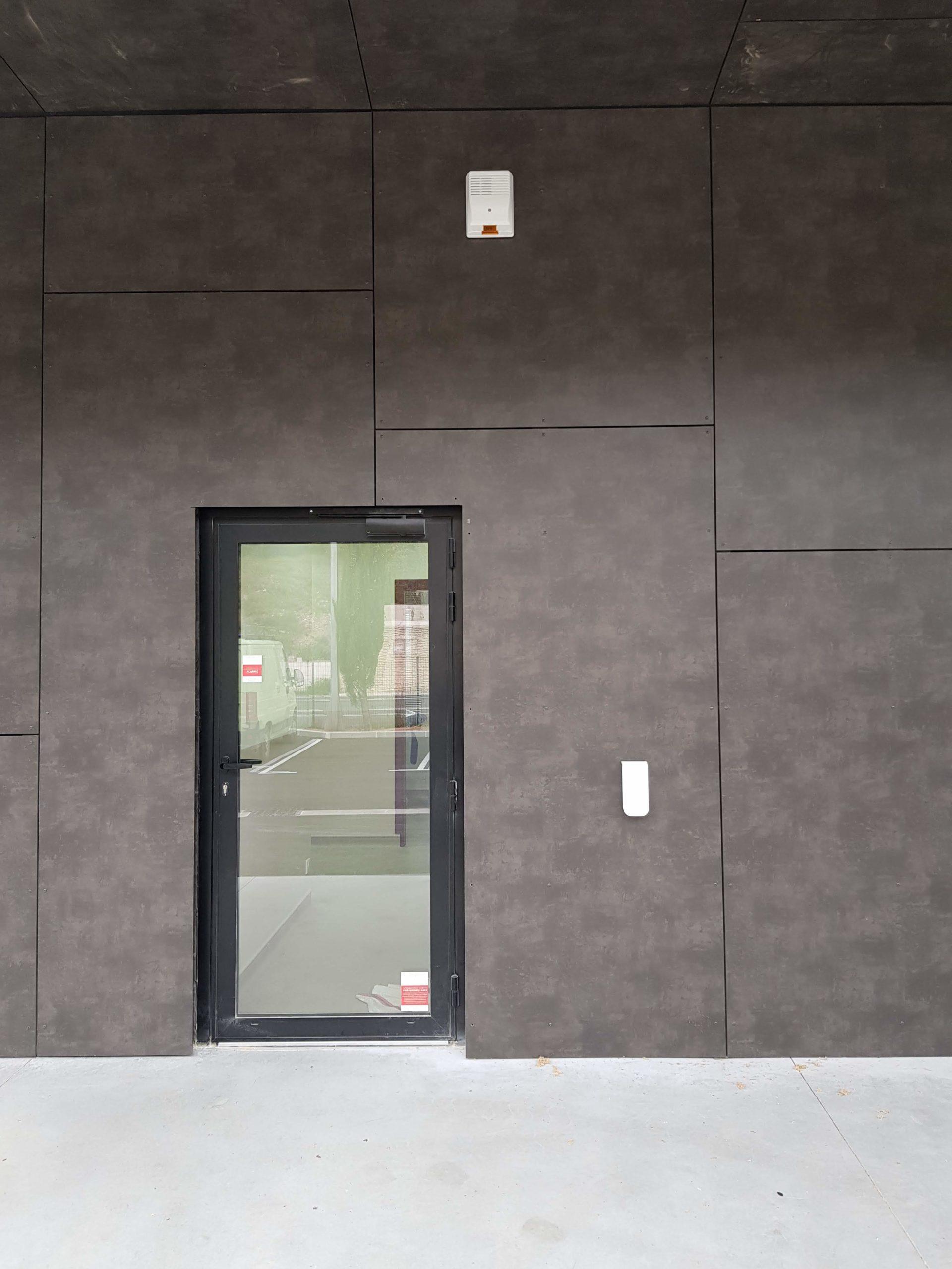 Vue d'une façade de la clinique avec la protection d'une alarme extérieure, la sirène extérieure Sirex et un détecteur linéaire Optex Bxs filaire